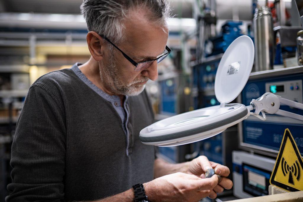Entwickler betrachtet im Labor ein Werkstück unter dem Vergrößerungsglas