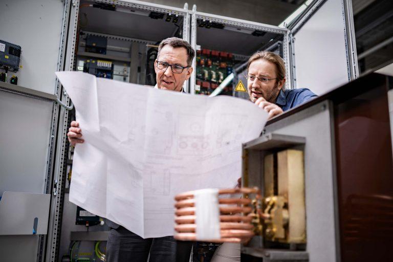 Zwei Entwickler über einen Plan gebeugt